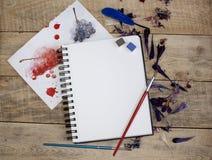 Чистый лист бумаги для текста с лепестками цветка на деревянной предпосылке Иллюстрация хобби, чертежа и воодушевленности Верхняя Стоковое Изображение RF