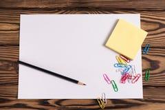 Чистый лист бумаги и опорожняет желтые квадратные стикеры и серию покрашенных бумажных зажимов и одного черного карандаша на стар Стоковое Фото