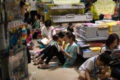 Читать в толпить Bookstore Стоковые Изображения