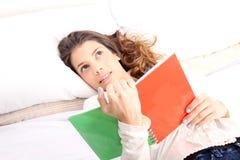 Читать книгу в кровати Стоковые Фото