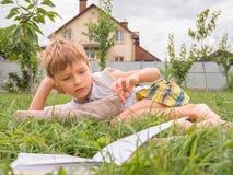 Читать концепцию книги Опубликовывая предпосылка Умный ребенок читая книгу внешнюю на траве стоковое фото rf