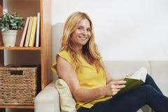 Читать усмехаясь женщину стоковое фото