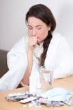 Чихать и пилюльки молодой женщины на таблице Стоковое Фото
