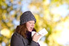 Чихая дерево молодой женщины outdoors Стоковое Изображение RF