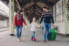 3 члена семьи на железнодорожном вокзале Счастливые мать, дочь и отец имеют положительные выражения лица, ожидания для поезда дал стоковая фотография rf