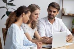 Члены клиента и компании обсуждая усаживание на столе используя подол стоковое изображение rf