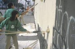 Члены Ommunity участвуют в надписи на стенах заволакивания Стоковое фото RF