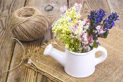 Чонсервная банка белой вазы моча с цветками на деревянном столе Стоковое Изображение