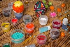 Чонсервные банкы краски, яркие блески, покрасили пасхальные яйца, конфеты на древесине Стоковые Фотографии RF