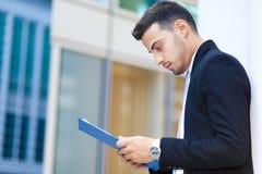 Чтение бизнесмена внешнее некоторые документы Стоковые Изображения