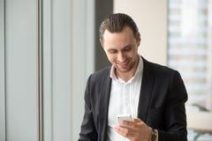 Чтение бизнесмена и сообщения посылки на телефоне Стоковые Изображения