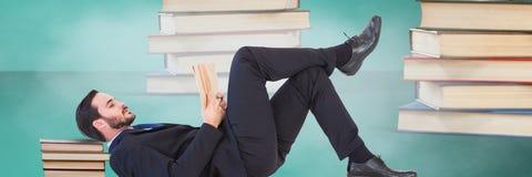 Чтение бизнесмена окруженное кучами книг и зеленой предпосылки стоковое фото rf
