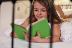 Чтение в кровати, малая глубина маленькой девочки Стоковая Фотография RF