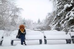 Чтение в снеге, усаживание девушки на стенде Стоковые Фотографии RF