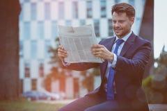 чтение газеты бизнесмена счастливое Стоковые Изображения