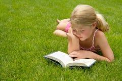 Чтение девушки в траве Стоковое Изображение