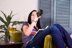 чтение девушки книги выпивая Стоковое Изображение