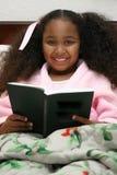 чтение девушки кровати стоковое изображение
