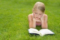 Чтение девушки outdoors Стоковое Фото