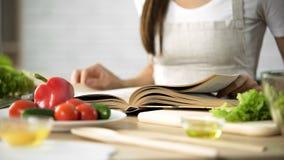 Чтение домохозяйки варя книгу с свежими овощами и инструментами кухни на таблице Стоковые Фото