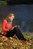 Чтение девушки в парке осени Стоковое Фото