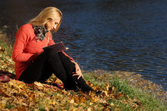 Чтение девушки в парке осени Стоковое фото RF