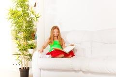 Чтение девушки на кресле Стоковые Изображения
