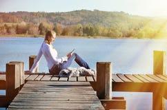 Чтение девушки от таблетки на деревянной моле Стоковое Фото