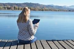 Чтение девушки от таблетки Стоковые Фотографии RF