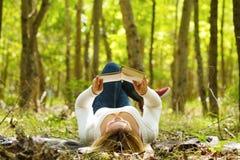 Чтение женщины в лесе Стоковая Фотография