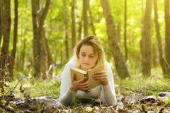 Чтение женщины в лесе Стоковое Фото