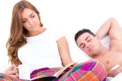 Чтение женщины в кровати с кофе пока человек спит Стоковые Изображения RF