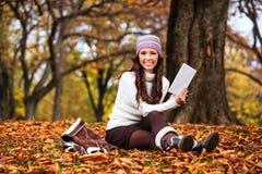 Чтение женщины в парке осени Стоковое Фото