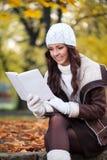 Чтение женщины в парке осени Стоковое Изображение