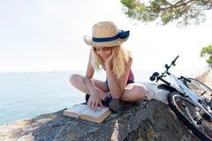 Чтение женщины изображения на морской дамбе стоковое изображение