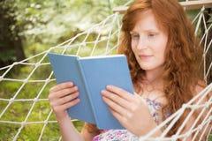 Чтение женщины на гамаке во время лета Стоковые Фото