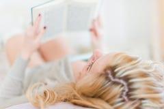 Чтение женщины на кровати Стоковые Фото