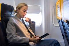 Чтение женщины на цифровом e-читателе пока путешествующ самолетом стоковые фото