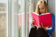 Чтение женщины на windowsill стоковые изображения rf