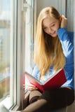 Чтение женщины на windowsill стоковые изображения