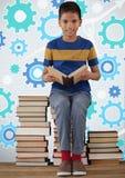 Чтение и усаживание мальчика на книге возвышаются перед установками шестерни cog Стоковая Фотография RF