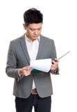 Чтение концентрата бизнесмена Азии на доске сзажимом для бумаги стоковое изображение rf