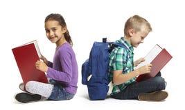 Чтение мальчика и девушки школы сидя Стоковые Изображения RF