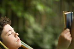 Чтение мальчика подростка в гамаке Стоковое Изображение
