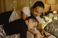 Чтение матери и мальчика на телефоне в кровати перед идти спать Стоковая Фотография
