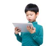 Чтение мальчика Азии на таблетке Стоковое Изображение