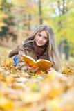 Чтение молодой женщины лежа на листьях Стоковое фото RF
