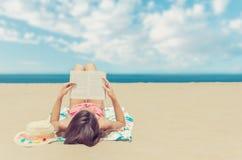 Чтение молодой женщины расслабляющее книга на пляже стоковое фото