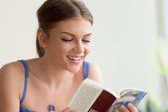 Чтение молодой женщины с новой книгой интереса Стоковое фото RF