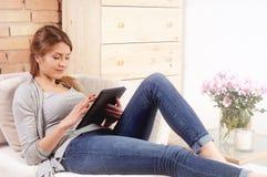 Чтение молодой женщины что-то на ее планшете Стоковые Фотографии RF